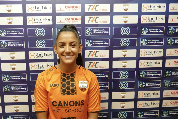 Rosie Kmita in front of Sponsors board after signing for London Bees