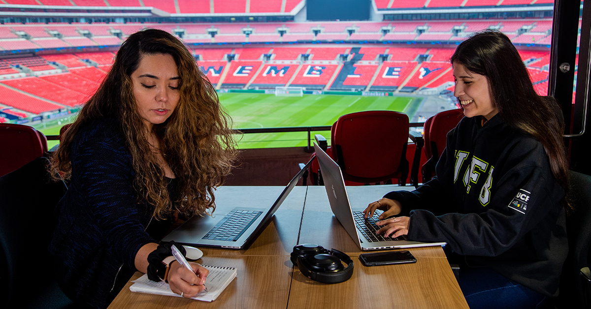 Two UCFB students studying overlooking Wembley Stadium Pitch