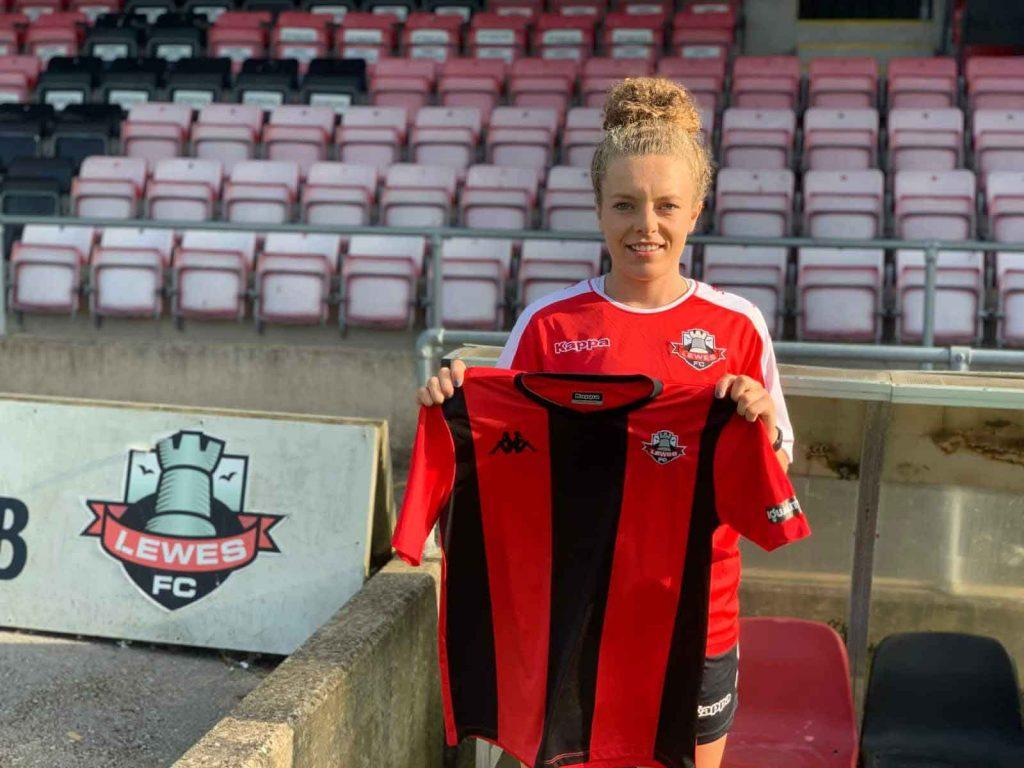 Emily Donovan holding up Lewses FC Women shirt