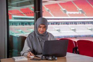 UCFB student working on laptop at Wembley Stadium