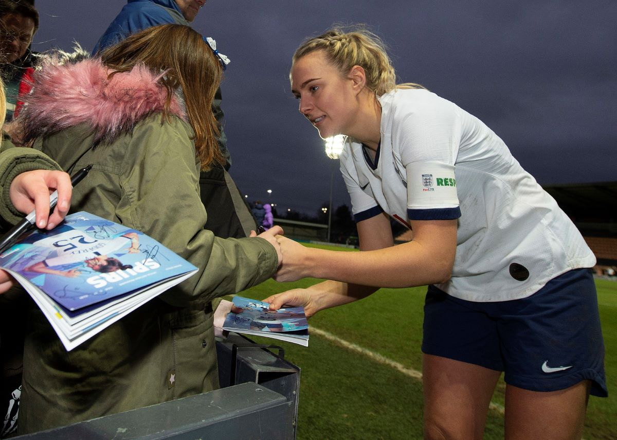 Josie Green signs a programme for a fan